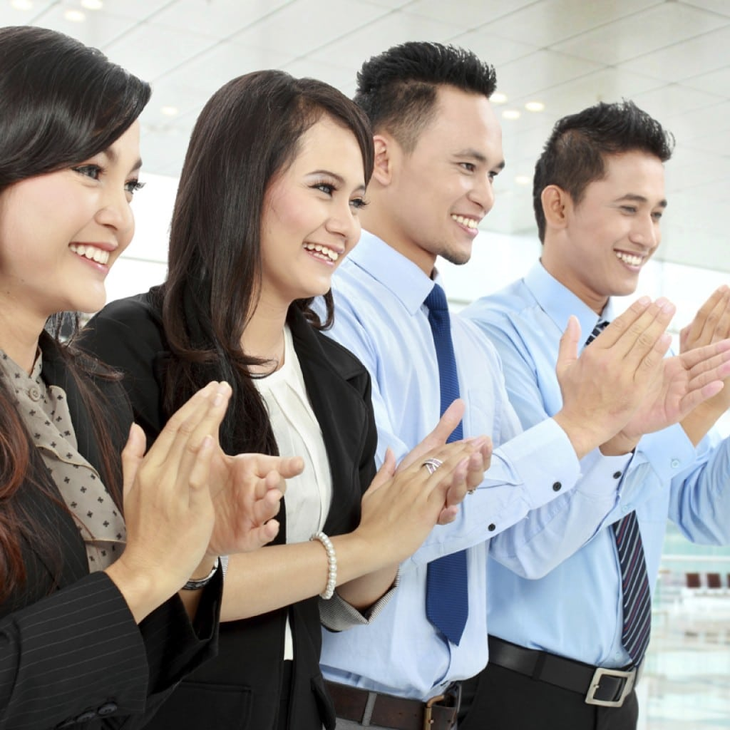 Portrait of a woman and man office workers  clapping celebrating success in the office